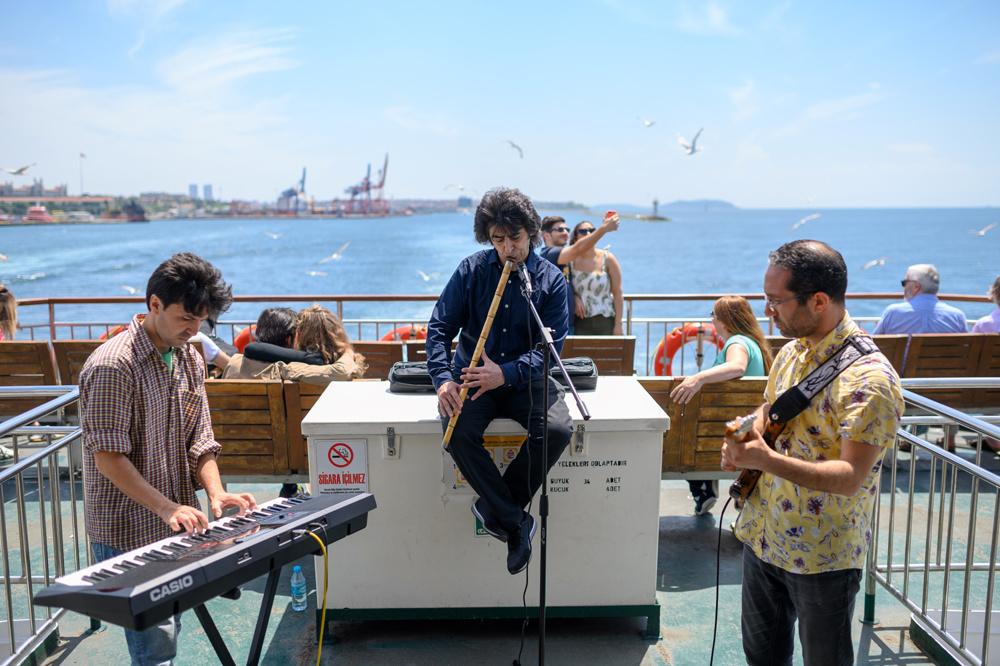 Oguzhan Erdem joue du ney, Eren Koc du clavier et Zafer Saka de la guitare lors d'un voyage en ferry sur le Bosphore de Kadikoy à Eminonu, à Istanbul. C'est déjà l'un des plus grands trajets en ferry au monde entre l'Europe et l'Asie, qui offrent à un quart de million de passagers quotidiens des vues inoubliables sur le chemin du travail. Et maintenant, l'expérience est devenue encore plus charmante., AFP