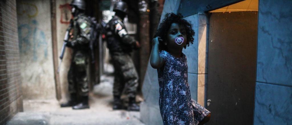 Een meisje uit de Rocinha favela in Rio de Janeiro is onderweg naar huis, terwijl achter haar enkele soldaten op patrouille zijn., Getty