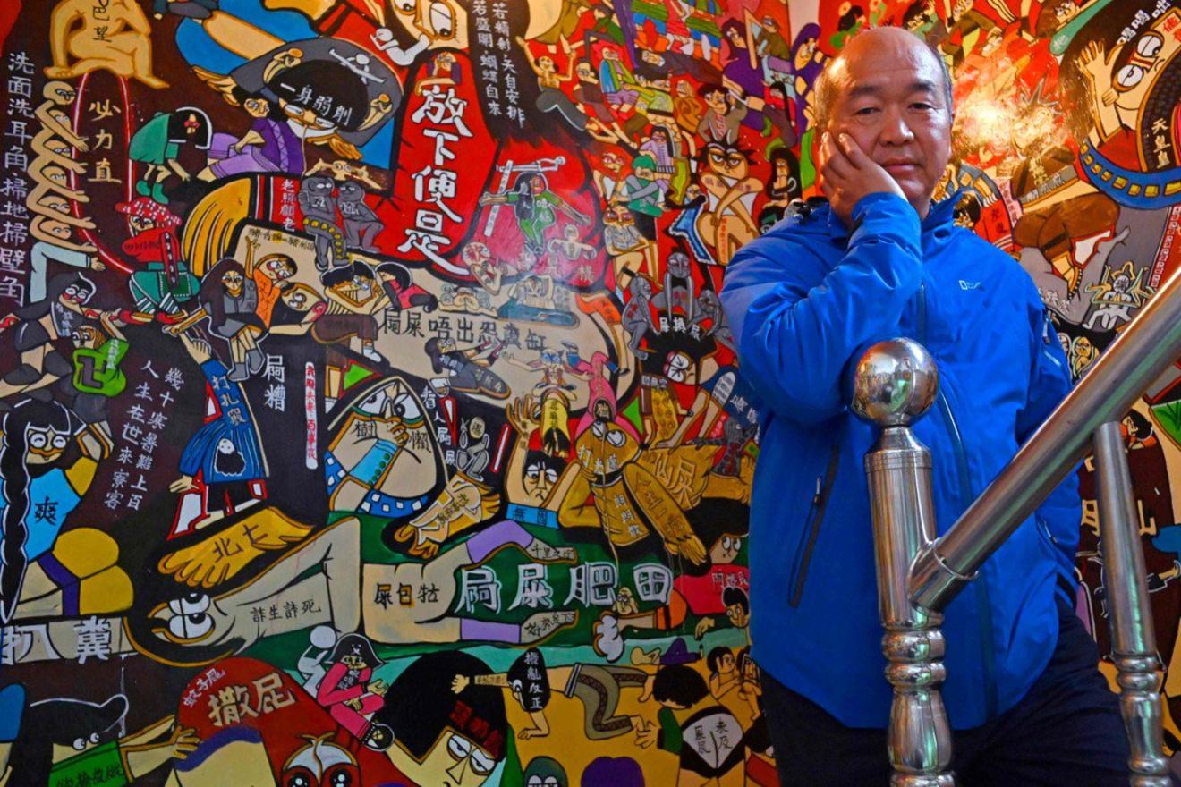 Taiwanese graffiti-artiest Wu Tsun-hsien poseert voor een versierde muur, AFP