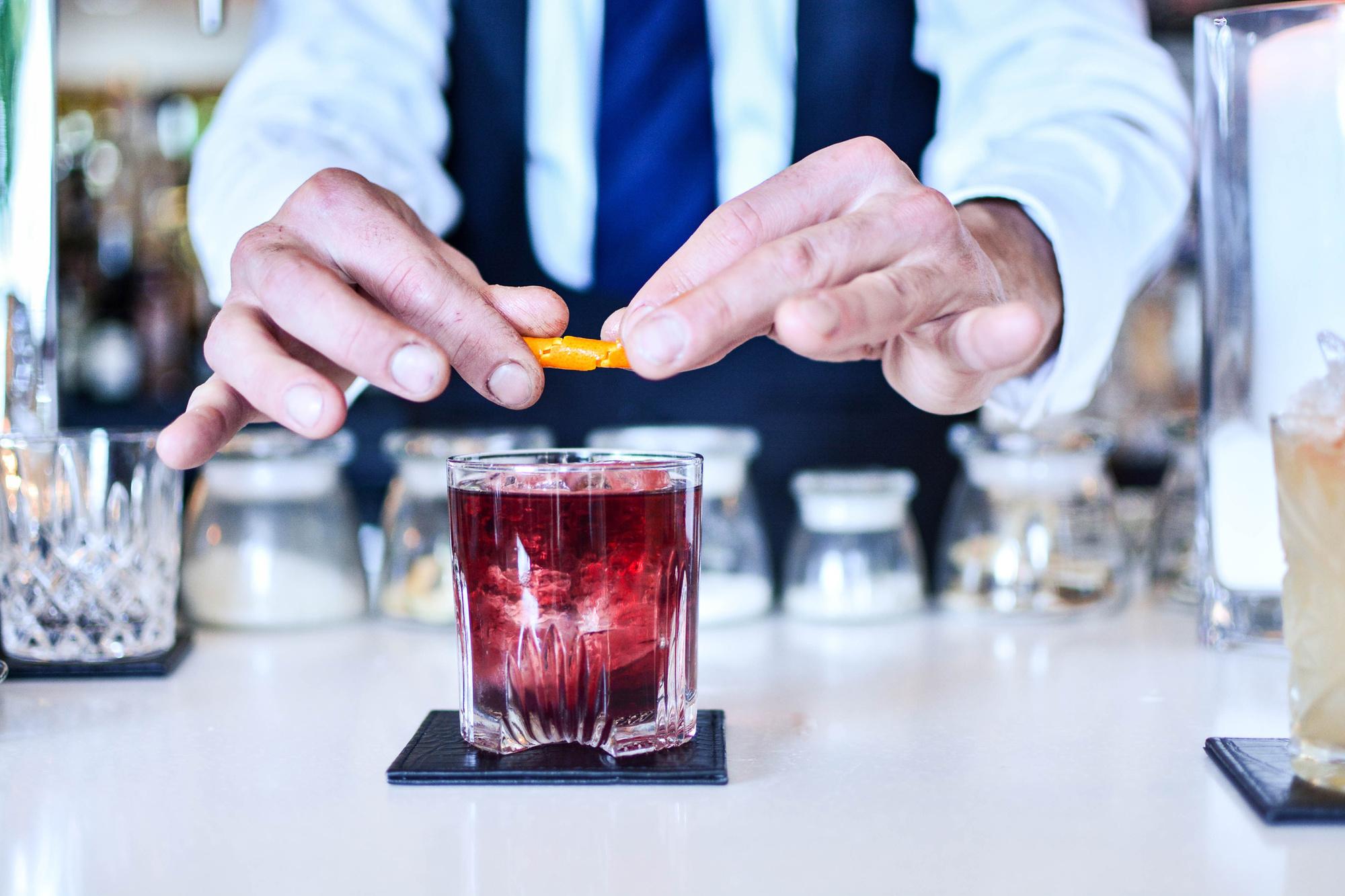 Barman serveert Negroni cocktail, Getty