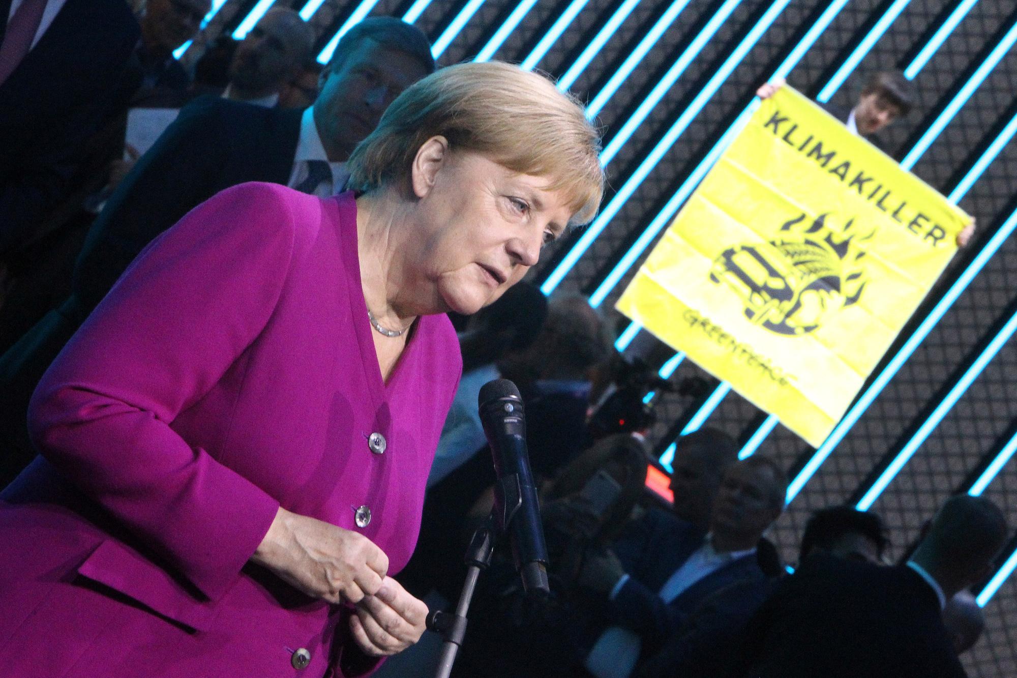Un activist de Greenpeace monte avec son affiche sur le toit d'une voiture pendant la visite d'Angela Merkel, belga
