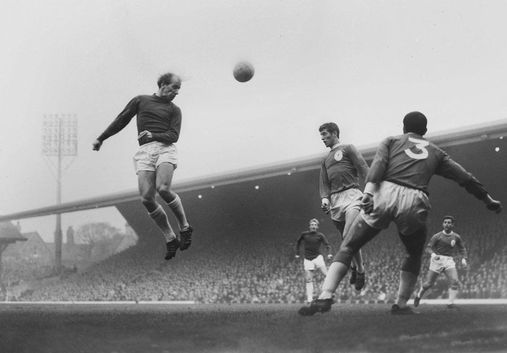 Een krachtige kopbal van Bobby Charlton, in en tegen Liverpool in oktober 1964., belgaimage