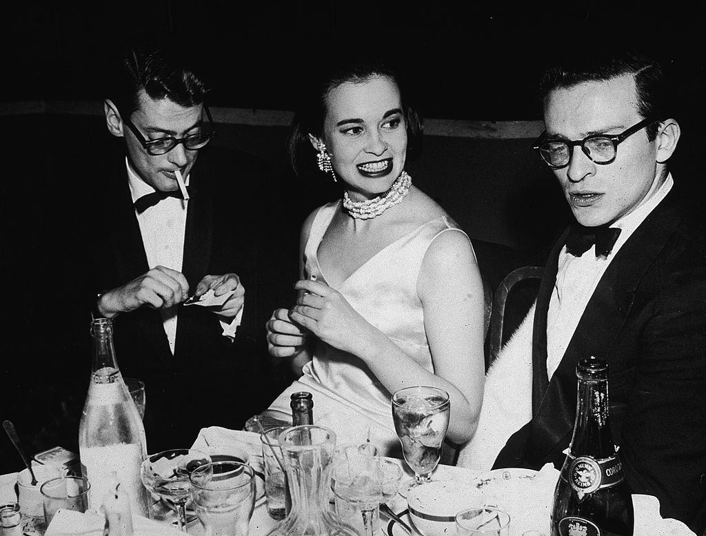 Fotograaf Richard Avedon (links), Gloria Vanderbilt en regisseur Sidney Lumet tijdens een feestje voor de première van 'East of Eden' (1955), Getty