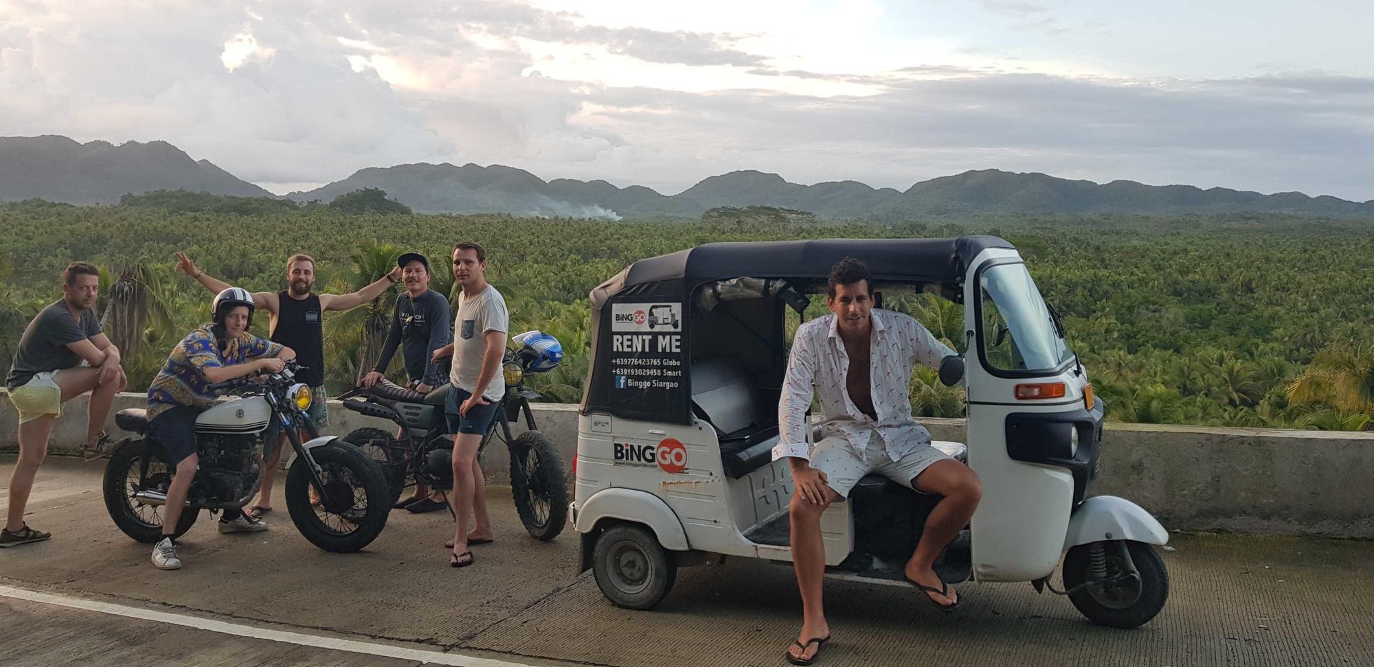 Een recente prospectie voor een nieuwe tuktuk-trip. Charles leunt op de tuktuk, Simon zit op de moto., Travelbase
